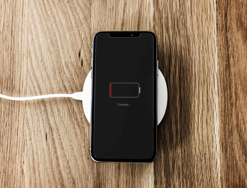 technology fix for wireless charging black cell phone low on battery laying on white charger
