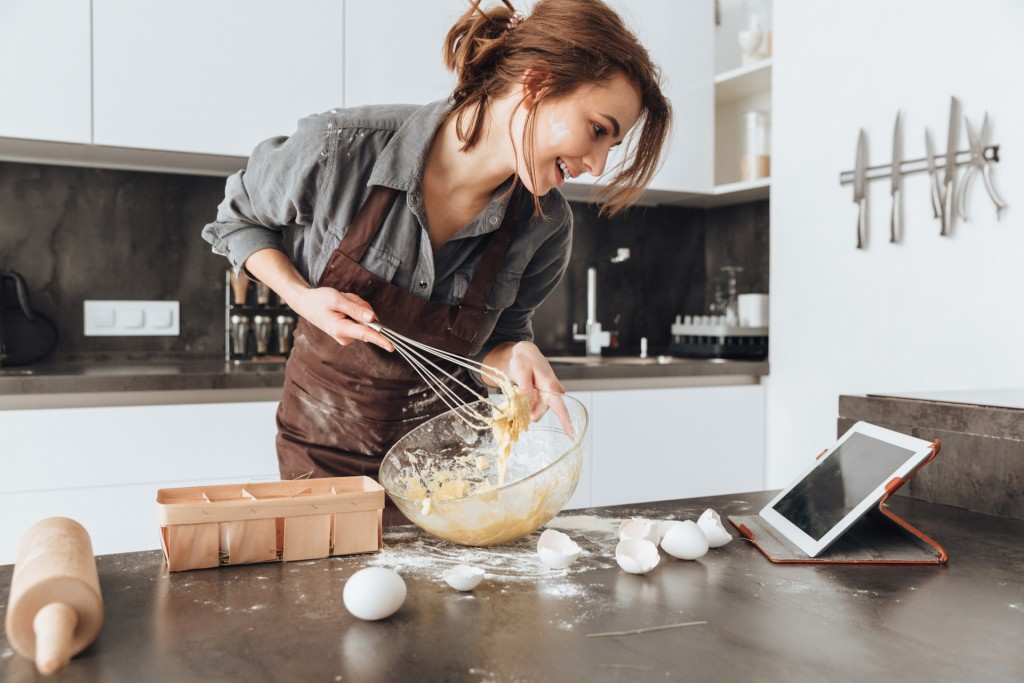Woman baking using old tablet as a digital cookbook